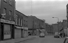 Meath Street towards The Coombe 1977. John Ryan's was recently an off-licence beside the Fountain. The two houses beside it included Flag Alley, a small courtyard. The site is now being redeveloped as apartments (called Flag Alley). The buildings to the south were demolished.