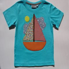Camiseta con barco. Camiseta azul de algodón con un dibujo de un barco, hecho de aplicaciones patchwork de telas de algodón también, y festoneado a mano con hilos dmc.