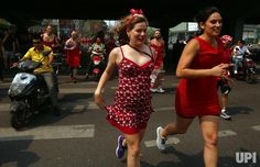 Both Chinese and foreign men and women wearing red dresses run through the streets of Beijing during the Hash Red Dress Charity Run on June…