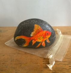 Gold fish painting on a river pebble