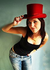 Woman with top hat and jeans.