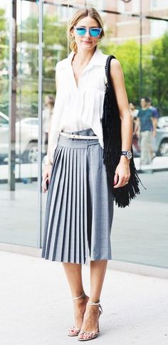 A white sleeveless blouse is tucked into a grey pleated skirt and worn with a white skinny belt, black fringe bag and metallic sandals.