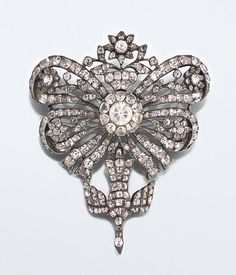 An 18th century topaz brooch  The surmount of sévigné design suspending a St. Esprit drop, set throughout with colourless topaz, mounted in silver with foil backs, possibly Iberian