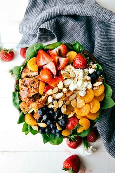 A healthy and incredibly simple spinach salad topped with chicken breast, strawberries, blueberries, toasted almonds, feta cheese, clementines, a squeeze of lemon, and a balsamic vinegar dressing.