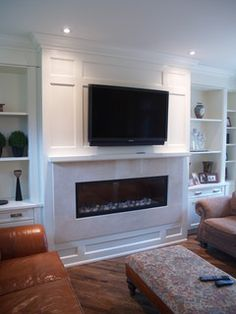 House of Fine Carpentry installed a feature wall around a fireplace insert with custom built in cabinetry.