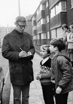 Michael Caine signing autographs for children near the Elephant and Castle. A scene from the ITV documentary 'Candid Caine', 1969.