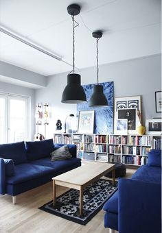 Colorful and bright living room with blue couches, industrial lamps and cool artworks.