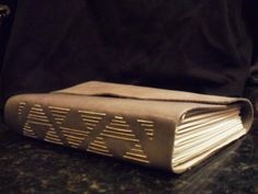 Long stitch leather book with geometric binding 8x5x2. The book consists of 11 signatures, and iis made of soft grey leather.