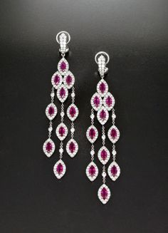 Vibrant color is captured in these exquisite gemstone and diamond earrings from Istana Private Collection, showcasing rubies surrounded by round diamonds in white gold. Jewelry Design Earrings, Garnet Jewelry, Modern Jewelry, Fine Jewelry, Ruby Earrings, Diamond Earrings, Hanging Earrings, Ring Set, Jewelery