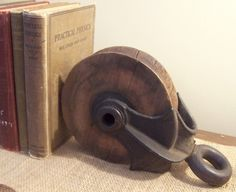 Neat idea to use something like this as a book end.  Pulley Vintage - Barn Industrial Shabby Chic Antique Rustic Farm House Bookend Pully. $35.00, via Etsy.