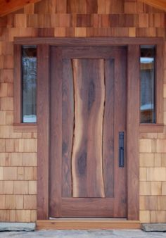A thick walnut slab, complete with live edges, flows down the center of the entry door on Dan and Beth's home.