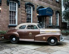 This Classic Police Car Photography is an image of an old Chevrolet parked outside an even older Police Barracks in Savannah, Georgia, I love the contrast of the brick wall and the rootbeer colored ca