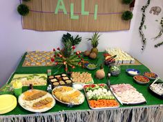 Tropical decor, animal toys, and grass skirting (from hula skirts) for the food and dessert table at baby's jungle themed birthday party. #decor #diy #firstbirthday