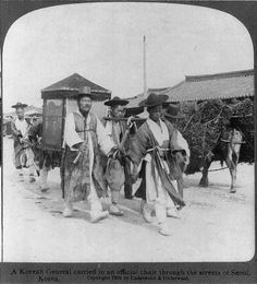 A Korean General carried in an official chair through the streets of Seoul…