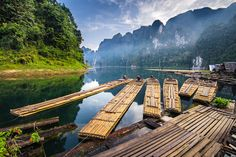Bamboo rafts moored to a deck with mountains behind