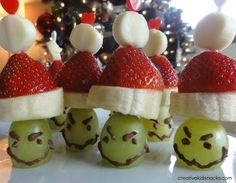 """These healthy fruit Grinch party poppers are based on Dr. Seuss' book """"How the Grinch Stole Christmas.""""  These cute treats can be made using the following ingredients:  white string cheese, strawberries, banana slices, green grapes, melted chocolate, and a tooth pick.  From:  Creative Kids Snacks"""