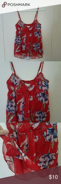 Abercrombie Red Floral Tank Top Abercrombie & Fitch red, white and blue floral tank top with adjustable straps.  Two layers of sheer red fabric.  Adorable knotted front and beaded bust.  Adjustable straps.  Stretchy bustline.  Two flaws noted in last two pictures.  1st: A few of the beads are missing on the left breast.  2nd: Underneath the right strap on the back, bustline is a little frayed and coming apart.  It isn't very noticeable though and could probably be fixed!  It's still a…