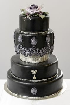 Black vintage style wedding cake with Swarowski crystals and sugar flower on the top. Lace-like antique fringe and cameos are all handmade. http://www.ditaleecakes.com