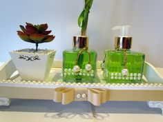 Lindo Kit para Lavabo, inclui: <br> <br>1 difusor com varetas, 120ml no vidro decorado com pérolas, essência a ser escolhida, <br>1 sabonete liquido, 120ml no vidro decorado com pérolas, essência a ser esolhida, <br>1 vasinho com cactos de silicone e acabamento com pedrinhas branca e, <br>1 bandeja no tamanho de 27x17cm, pintada à mão e decorada com gorgurão e pérolas e pés de resina. <br> OBS: devido a grande demanda de final de ano o modelo dos vidros de sabonete e difusor pode alterar…