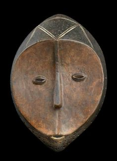 Lega, Dem. Rep. Congo: A 'Bwami' society mask.  Among the Lega inhabiting the Eastern Congo, social life is determined by the 'Bwami' society. (The society has six ranks for men and three for women; with transition rites). Miniature masks serve as a kind of identification while large masks such as the above are the prerogative of the two highest ranks in 'Bwami' society. The above, large Lega-mask displays the characteristic heart-shaped, concave face...