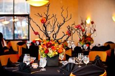 Color Palette: Orange and Black Black tablecloths with orange chair sashes set the scene, but we can't take our eyes off this dynamic centerpiece with branches, suspended candles, and bold florals.