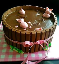 This link has the recipe and instructions: as happy as a pig in mud, pigs, kit kat cake, dessert, chocolate, marzipan pink pigs in barrel, kitkat, pink gingham ribbon