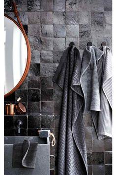 Une salle de bains dominée par le gris, de beaux carreaux à l'aspect artisanal, une touche de cuivre et de bois. Contraste élégant.