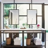 Vanity in front of window with ceiling mounted mirrors.