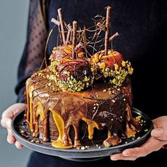 Sweet treats aren't just for trick or treaters! This showstopping cake dripping with layers of caramel and chocolate, and a centrepiece of sticky, sweet toffee apples, is wickedly irresistible. | Tesco