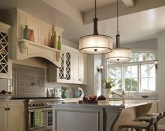For a large kitchen island consider two pendant lights instead of your typical three mini-pendants that we are so familiar with. Love the coordinating sconces in the breakfast nook!