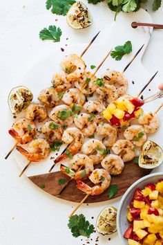 Savory, delicious Spicy Grilled Shrimp topped off with cilantro, lime, and a sweet minced tomato and pineapple sauce. This healthy recipe is perfect for a fun spring and summer weeknight dinner or having friends over! #shrimprecipes