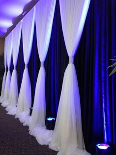Photos that inspire us…turn a boring wall into a fabulous backdrop with dramatic draping and uplights. #partyrentals #celebrations