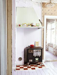 Porin Maija -puuhella, käytännöllinen laattamatto ja koristeellinen kristallikruunu luovat veikeän kontrastin tilaan. / Crystal chandelier brings fascinating contrast to the otherwise earthy kitchen. / Kuva/pic: Petra Tiihonen