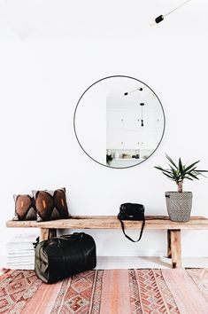 entryway // circle mirror // wooden bench // potted plant // decorative pillows // living room // living space // modern // boho
