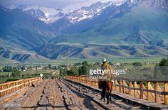 Stock Photo : Kyrgyzstan, At-Bashi. Kyrgyz shepherd crossing a wooden bridge…