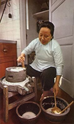 Grinding rice into flour, one of the cooks uses a granite mill, which serves much the same purpose in Chinese kitchens as a large mortar and pestle. It is also used for such tasks as making groundnut oil or bean paste.  From The Cooking of China, Time Life Foods of the World.