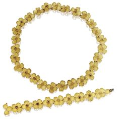18 KARAT GOLD 'DOGWOOD' NECKLACE AND BRACELET, TIFFANY & CO. The necklace and bracelet designed as textured gold dogwood flowers, gross weight approximately 121 dwts., bracelet length 6 7/8  inches, necklace length 17 inches, both signed Tiffany & Co.