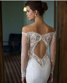 The keyhole back on this designer long sleeve wedding dress is amazing. The off the shoulder design flows well into the sheer beaded lace sleeves.  Embroidery & applique work like this can raise the price of a designer wedding gown significantly.  As USA dress makers we can produce elegant long sleeve wedding gowns like this for a very reasonable price. Custom designs & #replica wedding dresses are our specialty.  Contact us for pricing and details from our main web page at…