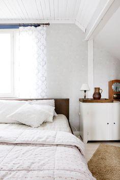 Yläkerrassa sijaitseva makuuhuone on tilava ja valoisa. Talosta löytyneestä vanhasta kaapista tuli yöpöytä. Kaapin päällä on Netan isoisän vanha kaappikello.