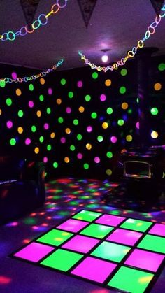 Neon dance party! I covered the walls in black tablecloth and used neon poster board for the circles and dance floor. Hung glowstick garland, added a disco ball light and LED blacklight, and we're ready to party!