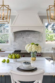 Beautiful backsplash. The backsplash tile is a 3″ x 6″ honed Cararra marble tile from Walker Zanger. White Kitchen with Stacked Cabinets and Grey Island