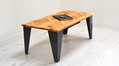 We made this coffee table from reclaimed parquet flooring. The table top sits on custom built steel legs. Suspended under the table is a storage...