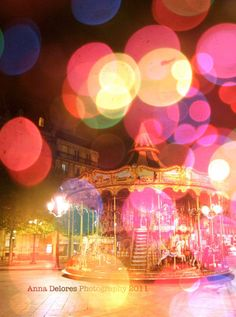 A hazy picture of a carousel & pink lights.