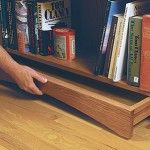 Hidden compartment drawer concealed under bookshelf