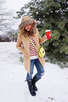 J. Crew Vail parka, hunter boots, pom hat, stripped top, yellow crossbody bag, ripped knee jeans, winter fashion