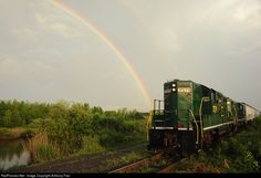 Raritan Central Railway's ex-PRR GP10 switches covered hoppers for Plastic Express as a rainbow forms to the East.