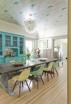 New fiberglass chairs contrast with this dining room's 1870s Italian worktable (which is 11 feet long!). The built-in cabinet (painted in Sea Wave Blue by Valspar) and the bird-themed wallpaper applied to the ceiling bring in a bit of whimsy that makes this room unforgettable.