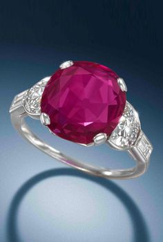 An art deco ruby single-stone ring, circa 1930. The cushion-shaped ruby, weighing 6.12 carats, between demi-lune and baguette-cut diamond shoulders. #ArtDeco