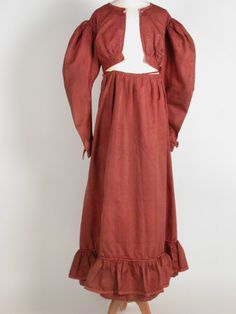 """Dress of brick-red silk with woven feather stripe and round neck. Front opening with button fastening at neck and hooks at slightly high waist; long sleeves, full at top with vandyked cuff; skirt with apron or fall front fastening with tapes. Flounced hem piping to shoulder seams, cuffs and hem flounce. Bodice lined in plain white silk. Alteration made; piece of plain white silk let in under arms. Probably re-modelled from a dress of slightly earlier date."" 1820 (circa)"