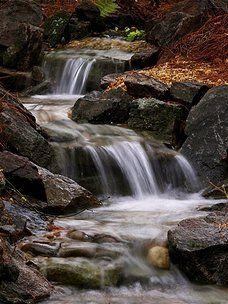 Beautiful backyard waterfalls by James Hughes Landscaping